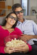 Couple On Sofa Watching TV Wearing 3D Glasses Eating Popcorn - stock photo