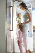 Mother And Daughter Choosing Snack From Fridge - stock photo