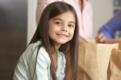Family Unpacking Grocery Shopping In Kitchen Stock Photos