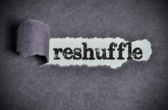 reshuffle word under torn black sugar paper - stock photo