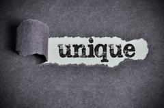 unique word under torn black sugar paper - stock photo
