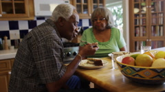 Mature black couple eating lunch together in kitchen Stock Footage