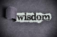 wisdom word under torn black sugar paper - stock photo
