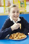 Female Pupil Eating Unhealthy School Lunch Stock Photos