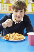 Male Pupil Eating Unhealthy School Lunch - stock photo