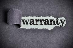 warranty  word under torn black sugar paper - stock photo