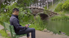 Man Sits On A Park Bench And Sketches On His Tablet By Beautiful Duck Pond Stock Footage