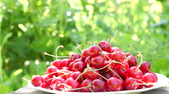Mouthwatering Cherries In A White Plate, On A Rustic Bench Stock Footage
