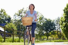 Attractive Mature Woman Riding Bike Along Country Lane Stock Photos