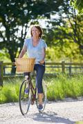 Attractive Mature Woman Riding Bike Along Country Lane - stock photo