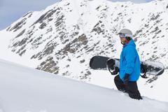 Man With Snowboard On Ski Holiday In Mountains Stock Photos