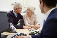 Senior Couple Meeting With Consultant In Hospital - stock photo