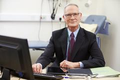 Portrait Of Male Consultant Working At Desk Stock Photos
