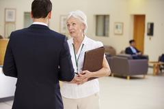 Two Consultants Discussing Patient Notes In Hospital - stock photo