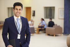 Portrait Of Male Consultant In Hospital Reception Stock Photos