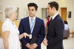 Three Consultants Meeting In Hospital Reception - stock photo