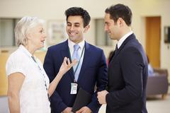 Three Consultants Meeting In Hospital Reception Stock Photos