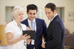 Three Consultants Discussing Patient Notes In Hospital - stock photo