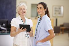 Female Consultant In Meeting With Nurse Using Digital Tablet Stock Photos