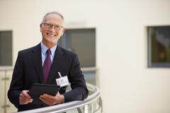 Portrait Of Male Consultant Using Digital Tablet In Hospital Stock Photos