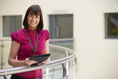Female Consultant Using Digital Tablet In Hospital Stock Photos