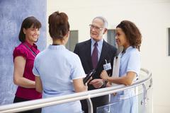 Consultants Meeting With Nurses Using Digital Tablet - stock photo