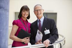 Two Consultants Meeting In Hospital Reception - stock photo