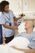 Nurse Adjusting Male Patient's IV Drip In Hospital - stock photo