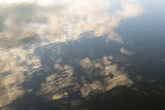 Water Ripples on a Village Pond with Cloud Reflection - stock photo