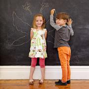Two little kids in front of blackboard with angel wings Stock Photos