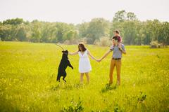 Happy family playing with black labrador dog in summer meadow. Father mother son Stock Photos
