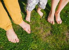 Stock Photo of Happy barefeet family standing on grass in warm summer day. Family concept.