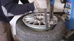 Mechanic in the service repair car wheel Stock Footage