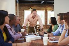 Male Boss Addressing Office Workers At Meeting - stock photo