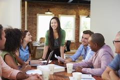 Female Boss Addressing Office Workers At Meeting - stock photo