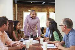 Male Boss Addressing Office Workers At Meeting Stock Photos