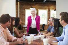 Senior Female Boss Addressing Office Workers At Meeting Stock Photos
