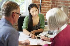 Senior Couple Meeting With Financial Advisor In Office Stock Photos