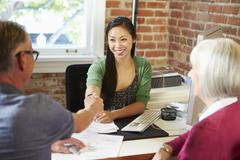 Senior Couple Meeting With Financial Advisor In Office - stock photo