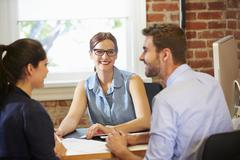 Couple Meeting With Financial Advisor In Office Stock Photos