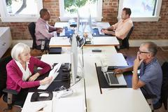 Group Of Workers At Desks In Modern Design Office - stock photo