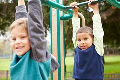 Two Young Boys On Climbing Frame In Playground - stock photo