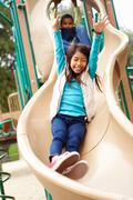 Young Girl Playing On Slide In Playground Stock Photos