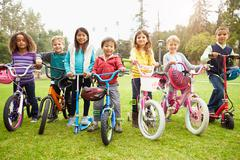 Young Children With Bikes And Scooters In Park Stock Photos