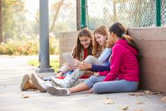 Group Of Young Girls Using Digital Tablet In Park Kuvituskuvat