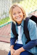 Portrait Of Young Boy With Rucksack Sitting In Park Stock Photos