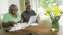 Mature black couple paying bills on laptop Stock Footage