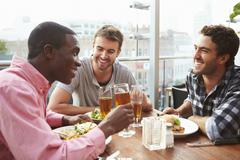 Three Male Friends Enjoying Lunch At Rooftop Restaurant Stock Photos