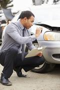 Loss Adjuster Taking Photograph Of Damage To Car Stock Photos
