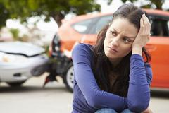 Worried Female Driver Sitting By Car After Traffic Accident - stock photo